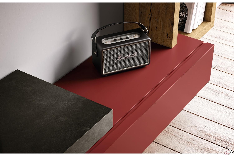Soggiorno moderno con cassetti rossi e panca sospesa metallizzata