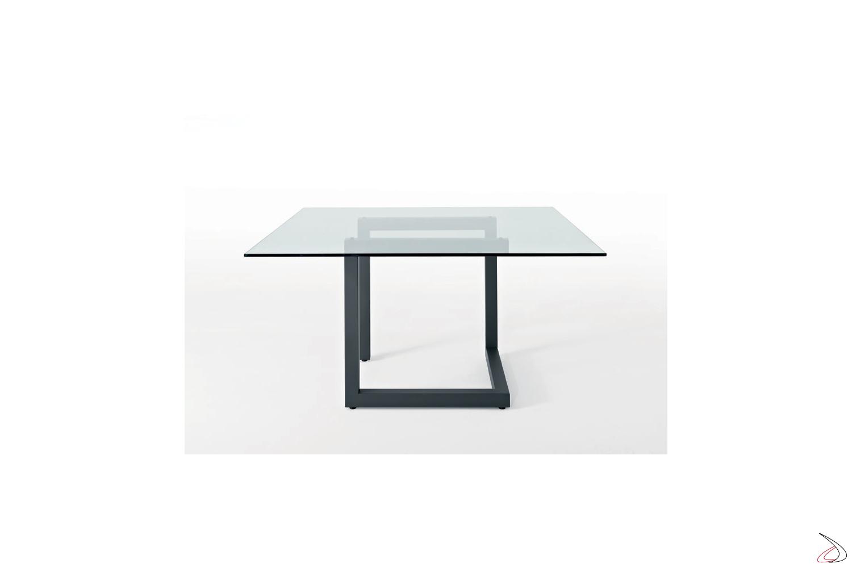Tavolo V6 con struttura centrale in metallo e piano in vetro.